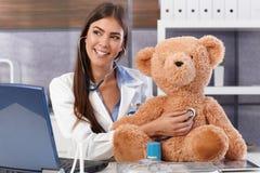 有玩具熊的笑的医生 免版税图库摄影