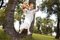 有玩具熊的红头发人女孩 库存图片