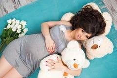 有玩具熊的美丽的怀孕的母亲 母性 免版税库存照片