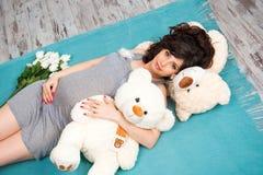 有玩具熊的美丽的怀孕的母亲 母性 库存图片