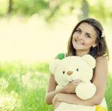 有玩具熊的美丽的青少年的女孩在绿草的公园。 免版税库存图片