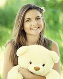 有玩具熊的美丽的青少年的女孩在绿草的公园。 图库摄影