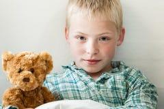 有玩具熊的逗人喜爱的年轻白肤金发的男孩 免版税图库摄影