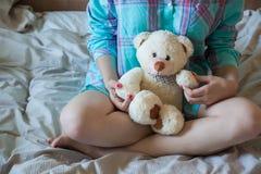 有玩具熊的年轻美丽的妇女在床上 图库摄影