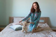 有玩具熊的年轻美丽的妇女在床上 免版税库存照片