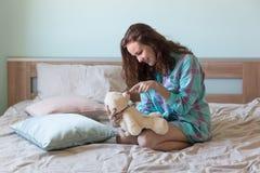 有玩具熊的年轻美丽的妇女在床上 库存照片