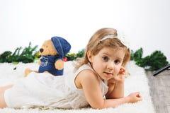 有玩具的女孩在地毯 免版税库存照片