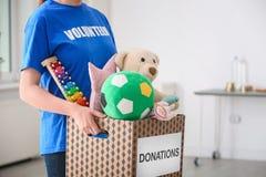 有玩具的女性志愿举行的捐赠箱子 免版税库存图片
