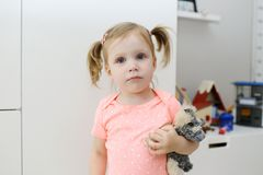 有玩具的小女孩在儿童` s屋子 图库摄影