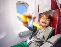有玩具的微笑的男孩飞行在喷气机飞机的飞行 免版税图库摄影