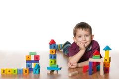 有玩具的聪明的小男孩 库存图片