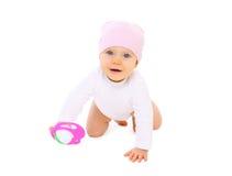 有玩具的逗人喜爱的微笑的婴孩在白色背景爬行 免版税库存图片