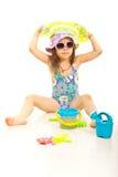 有玩具的逗人喜爱的海滩女孩 免版税库存照片