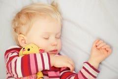 有玩具的逗人喜爱的睡觉的白肤金发的婴孩 库存照片
