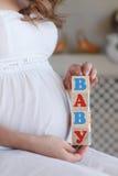 有玩具立方体的孕妇在手上 图库摄影