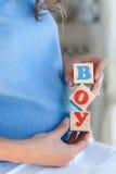 有玩具立方体的孕妇在手上 免版税图库摄影