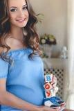有玩具立方体的孕妇在手上 免版税库存图片