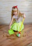 有玩具笤帚和平底锅的可爱的小女孩 免版税库存照片