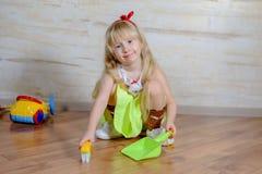 有玩具笤帚和平底锅的可爱的小女孩 库存图片