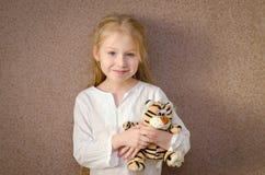有玩具老虎的小女孩 免版税库存照片