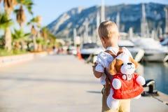 有玩具背包的逗人喜爱的白肤金发的男孩 免版税库存照片