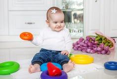 有玩具金字塔的微笑的婴孩是 童年devel的概念 免版税库存照片