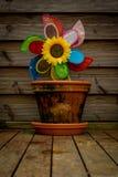 有玩具风车和向日葵的花盆 图库摄影