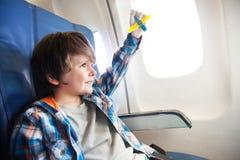有玩具飞机的小微笑的男孩由窗口 图库摄影