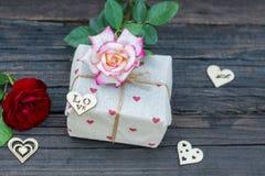 有玫瑰和心脏的土气礼物盒,在老木桌上 免版税库存图片