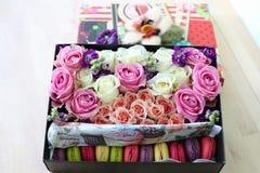 有玫瑰和蛋糕蛋白杏仁饼干的箱子 免版税库存照片