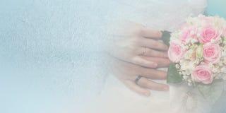 有玫瑰婚戒和花束的新娘和新郎手  库存照片
