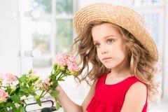 有玫瑰的一个小女孩 issitting在镜子附近的她 库存照片