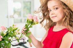 有玫瑰的一个小女孩 issitting在镜子附近的她 库存图片