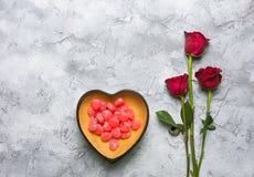 有玫瑰的红色心形的糖果碗 库存照片
