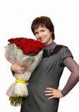 有玫瑰的美丽的微笑的妇女 免版税库存照片