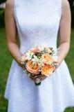 有玫瑰美丽的花束的新娘在她的手上 库存图片