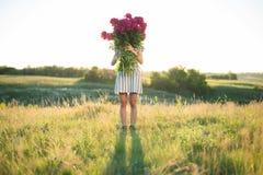 有玫瑰色牡丹大花束的妇女在日落的 免版税图库摄影