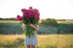 有玫瑰色牡丹大花束的妇女在日落的 图库摄影
