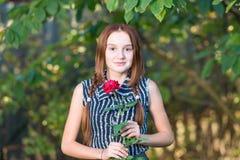 有玫瑰色花的美丽的愉快的少年女孩在庭院里 免版税库存照片