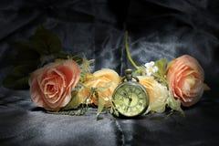 有玫瑰色花的葡萄酒口袋时钟在黑织品背景 时间概念爱  静物画样式 库存图片