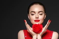 有玫瑰色花美丽的卷发和嘴唇的秀丽妇女 免版税库存图片