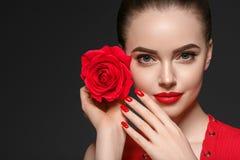 有玫瑰色花美丽的卷发和嘴唇的秀丽妇女 免版税库存照片