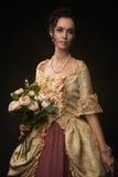 有玫瑰花束的典雅的减速火箭的Portet棕色毛发的妇女  免版税库存图片