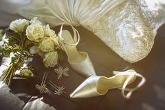 有玫瑰花束的婚礼鞋子在椅子的 免版税库存图片