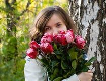 有玫瑰花束的少妇在桦树树干的 免版税库存图片