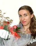 有玫瑰花束的愉快的妇女  免版税库存图片