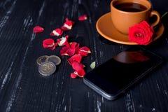 有玫瑰花瓣、手机和欧洲硬币的橙色咖啡杯在黑背景 免版税库存照片