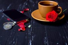 有玫瑰花瓣、手机和欧洲硬币的橙色咖啡杯在黑背景 免版税图库摄影