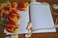 有玫瑰花瓣的笔记本 库存图片