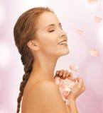 有玫瑰花瓣的美丽的妇女 免版税库存图片